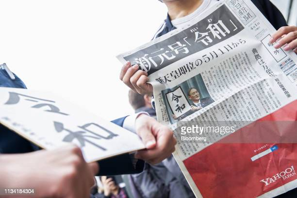 A man holds a copy of an extra edition of the Asahi Shimbun newspaper reporting on the announcement of the name of Japan's next imperial era Reiwa in...