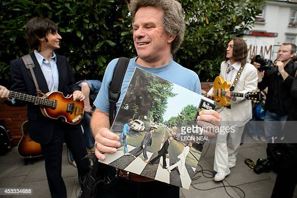 A man holds a copy of the Beatles album Abbey Road as the cast of the musical Let It Be preapre to perform near famous Abbey Road zebra crossing in...