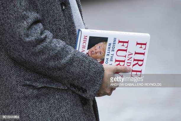 A man holds a copy of the book 'Fire and Fury Inside the Trump White House' by Michael Wolff after buying it at a bookstore in Washington DC on...
