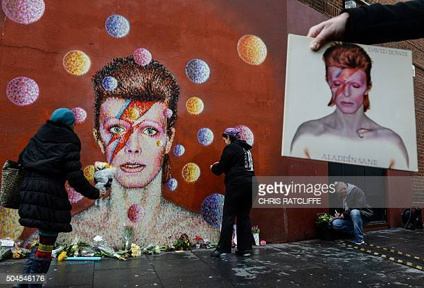 A man holds a copy of the David Bowie album 'Aladdin Sane' as floral tributes are left beneath a mural of British singer David Bowie painted by...