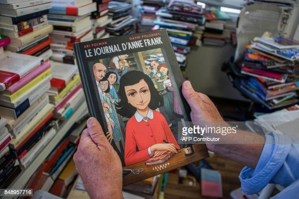 A man holds a copy of the graphic novel version of The Diary of Anne Frank by Israeli writerdirector Ari Folman and illustrator David Polonsky in...