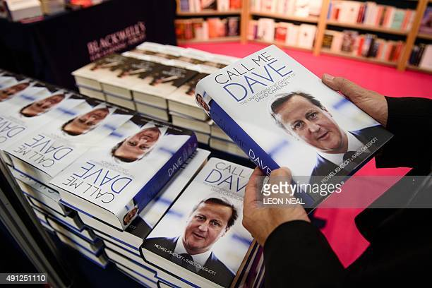 A man holds a copy of the unauthorised biography of British Prime Minister David Cameron entitled Call Me Dave by Michael Ashcroft and Isabel...