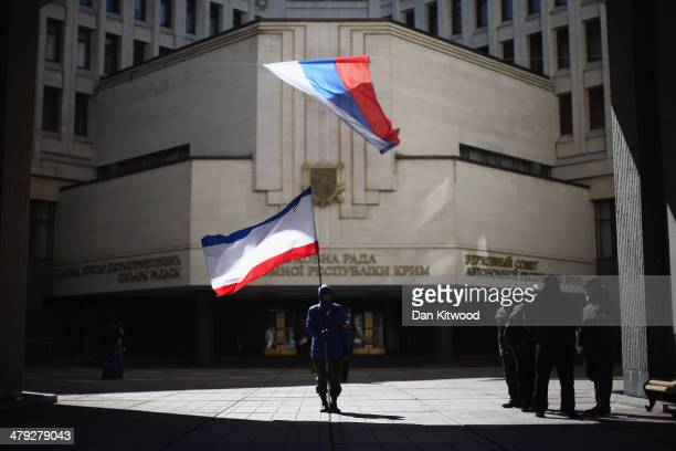 Man holds a Crimean flag in front of the Crimean parliament building on March 17, 2014 in Simferopol, Ukraine. People in Crimea overwhelmingly voted...