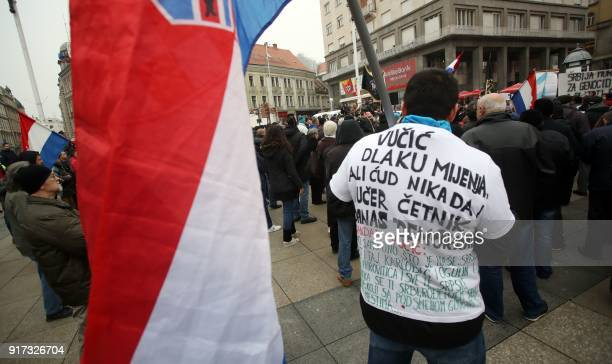 A man holds a Croatian flag and wears a tshirt on which is written a play of words with the name of the Serbian President Aleksandar Vucic which...
