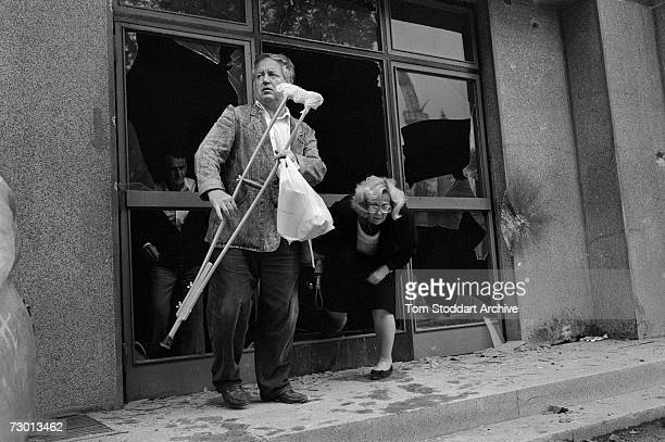Man holds a crutch as he waits for his wife to climb through a broken shop window on Sniper Alley. During the 47 months between the spring of 1992...