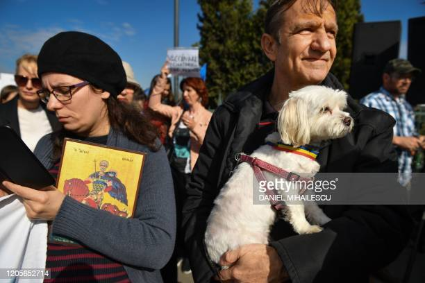 A man holds a dog wearing a Romanian flag during a demonstration against a draft law to be adopted by the Romanian Parliament which will make...