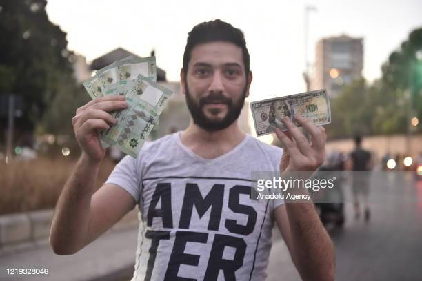 Man holds a dollar and Lebanese pounds as he poses for a photo during a protest against dire economic conditions and depreciation in the value of the...