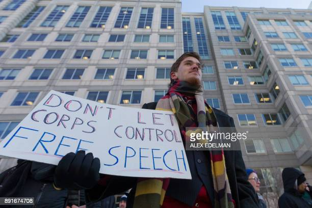A man holds a 'Don't Let Corps Control Free Speech' protest sign during a demonstration against the proposed repeal of net neutrality outside the...