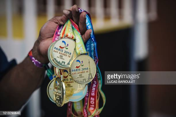 A man holds a dozen of gold medals during the synchronized swimming contest during the 10th edition of the international Gay Games at the Maurice...