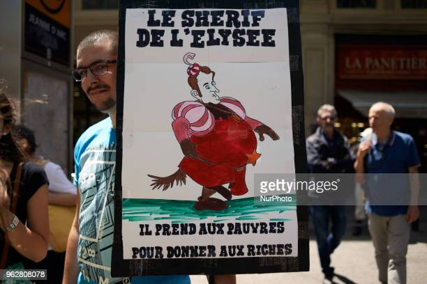 A man holds a drawing depicting French President Macron and reading 'Elysée's Sheriff he takes to poors for giving it to richs' A quotmaree...