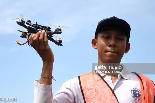 A man holds a drone during the FAI Drone Racing World Cup event in Denpasar on Indonesia's resort island of Bali on April 7 2018 / AFP PHOTO / SONNY...