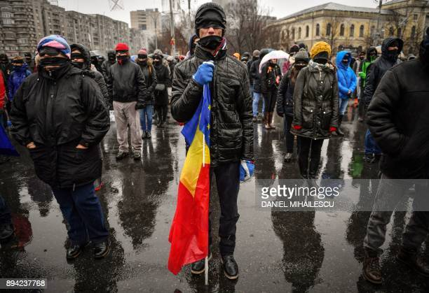 TOPSHOT A man holds a EU and a Romanian flag as people with their eyes and mouths covered with black cloth take part in a silent flash mob outside...