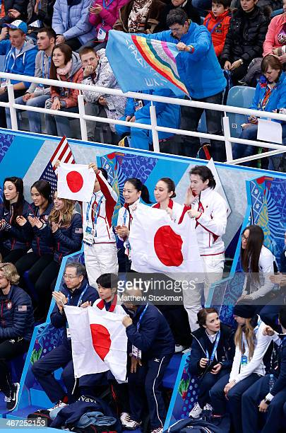 Man holds a flag above the Japanese team as Yuzuru Hanyu competes in the Figure Skating Men's Short Program during the Sochi 2014 Winter Olympics at...