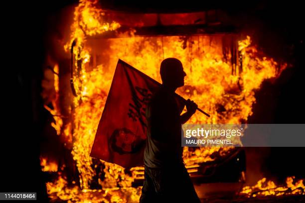 TOPSHOT A man holds a flag depicting former Brazilian President Luis Inacio Lula da Silva past a bus in flames during a protest organized by the...