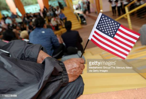 Man holds a flag during a children's citizenship ceremony at Children's Fairyland in Oakland, Calif., on Monday, July 29, 2019. The U.S. Citizenship...