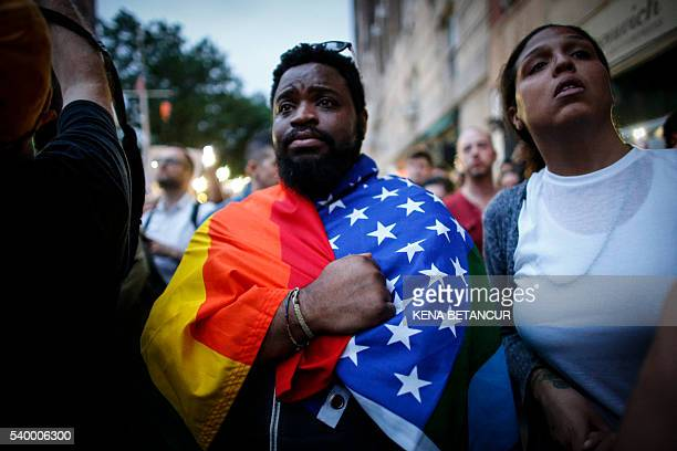 A man holds a flag during a vigil in solidarity for the victims killed at Pulse nightclub in Orlando in New York on June 13 2016 The American gunman...