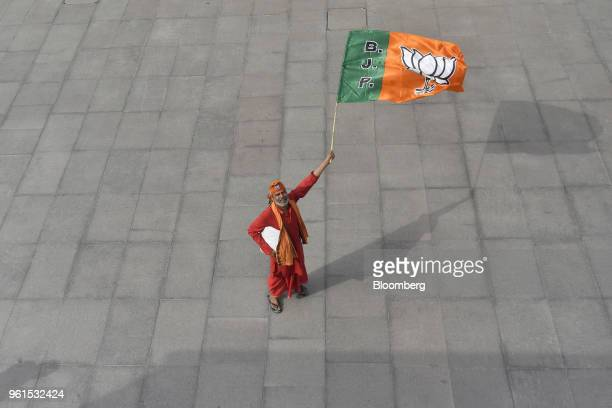 A man holds a flag of Bharatiya Janata Party at the courtyard of the party's headquarters in New Delhi India on Tuesday May 15 2018 While the BJP has...