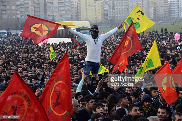 A man holds a flag of the Kurdish Worker's Party and a poster flag of jailed kurdish leader and PKK founder Abdullah Ocalan during a rally on January...