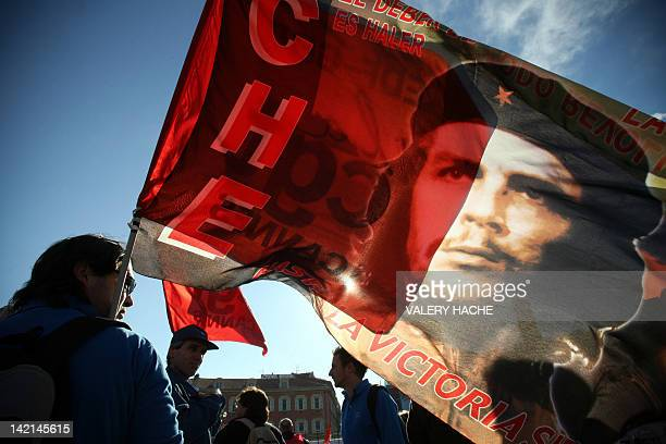 A man holds a flag representing the leftist revolutionary icon Ernesto 'Che' Guevara as people gather 14 November 2007 in Nice southern France on the...
