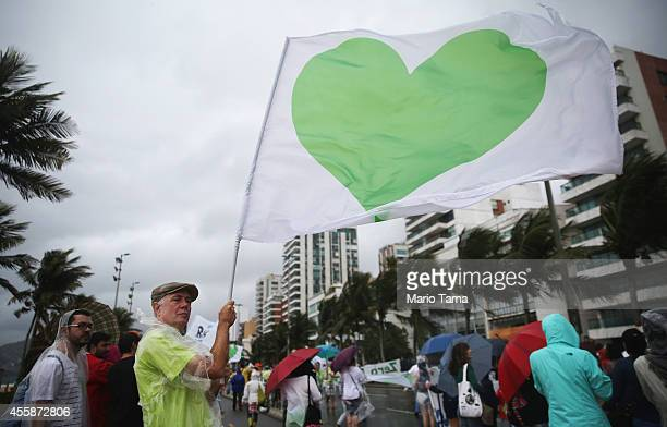 A man holds a flag with a green heart during the climate march along Ipanema beach on September 21 2014 in Rio de Janeiro Brazil Protests calling for...