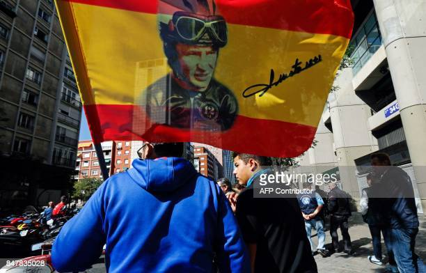 A man holds a flag with a portrait of Grand Prix motorcycling legend Angel Nieto during a tribute in front of the Santiago Bernabeu stadium in Madrid...
