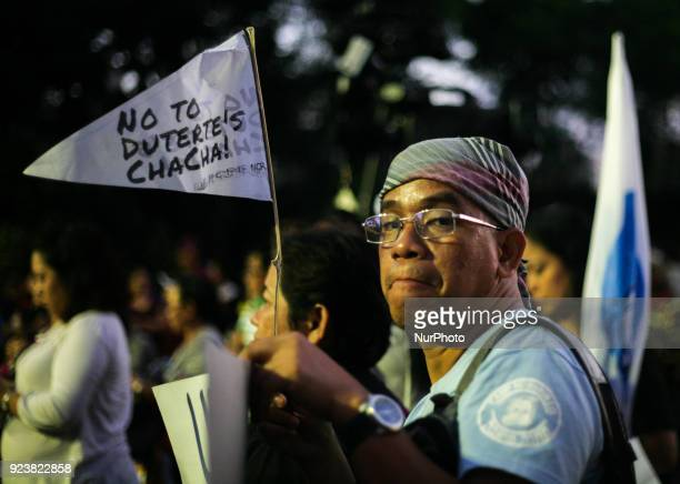 A man holds a flaglet protesting charter change during a demonstration ahead of the 32nd anniversary of the EDSA People Power Revolution at the...