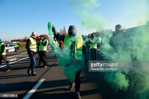 A man holds a flare as demonstrators wearing yellow vests protest against the rising of the fuel and oil prices on November 17 2018 in Haulchien near...