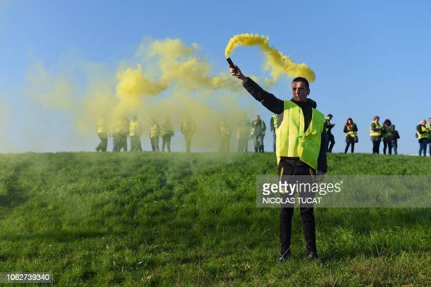 Man holds a flare during a demonstration of Yellow Vests against the rising of the fuel and oil prices on November 17, 2018 in Bordeaux, southwestern...