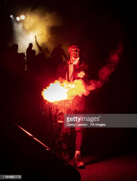Man holds a flare during a performance of Bivouac by French street arts G??n??rik Vapeur, one of the headlining performances at the Freedom Festival...
