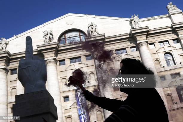 A man holds a flare next to the sculpture 'Love' or 'Il Dito' by Italian artist Maurizio Cattelan during a general strike of the public transport...