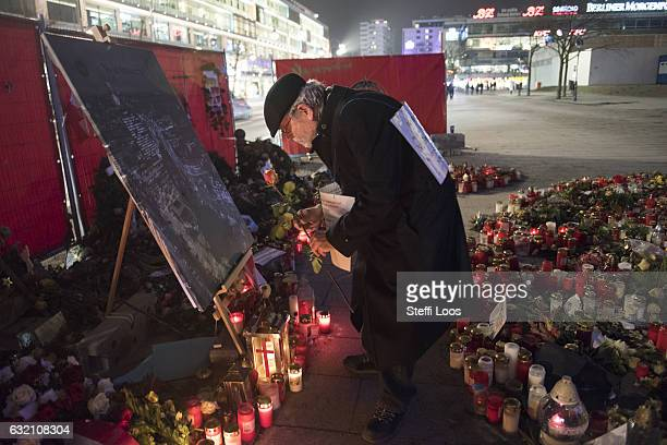 A man holds a flower at a memorial for the Christmas market terror attack victims at Breitscheidplatz on January 19 2017 in Berlin Germany On...