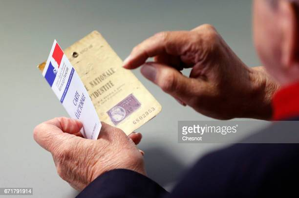 A man holds a French voter registration card and an identity card during the first round of 2017 French presidential election at a polling station on...