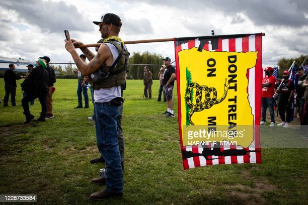 Man holds a Gadsden flag as several hundred members of the Proud Boys and other similar groups gathered for a rally at Delta Park in Portland, Oregon...