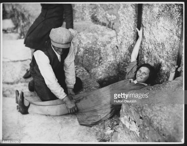 A man holds a girl's legs as she prepares to kiss the Blarney Stone The stone a block below the castle battlements must be reached by leaning over...