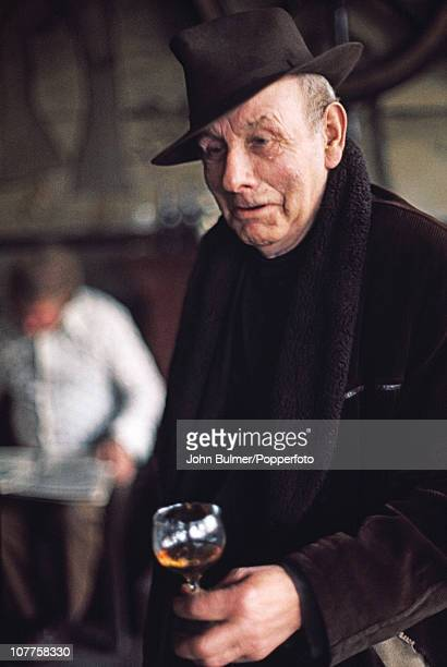 A man holds a glass in a pub in Manchester England in 1976