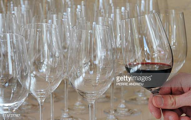 A man holds a glass of wine with SaintEmilion grand cru classe 'Chateau Cheval Blanc 2010' on April 4 2011 in SaintEmilion near Bordeaux during the...