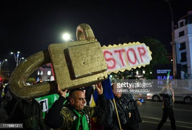 """Man holds a gold painted mock-up chainsaw reading """"STOP"""" during a protest against illegal logging in the forests of Romania gathering aroung 4,000..."""