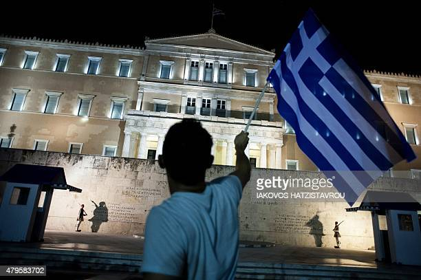 Man holds a Greek national flag as he celebrates in front of the parliament on July 5, 2015 in Athens after early results showed those who rejected...