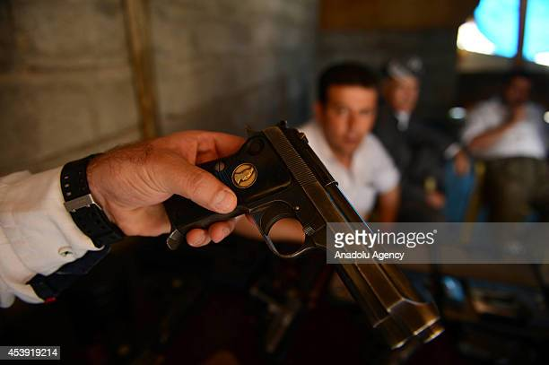 A man holds a gun at the Arbil Gun Bazaar in Kasnazan near the Arbil Iraq on August 20 2014 Dealers say that sales of weapons at the market have...