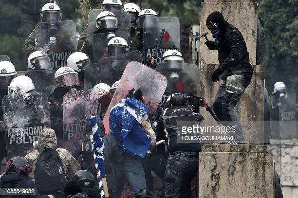 Man holds a hammer as protesters clash with riot police in front of the Greek Parliament in Athens on January 20, 2019 during a demonstration against...