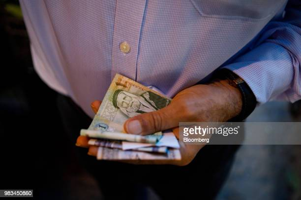 A man holds a handful of Jordanian dinar banknotes at a local fruit and vegetable market in Amman Jordan on Thursday June 21 2018 President Trump and...