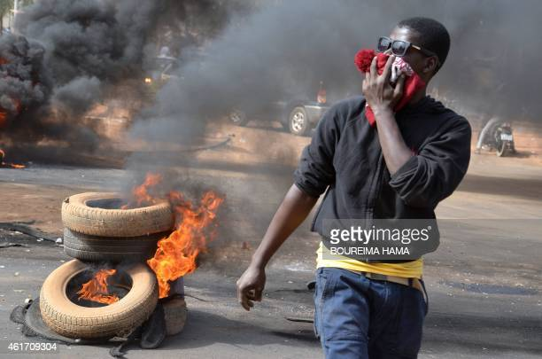 A man holds a hat over his mouth as black smoke billows from tyres set on fire in Niamey on January 18 2015 after police fired teargas to disperse a...