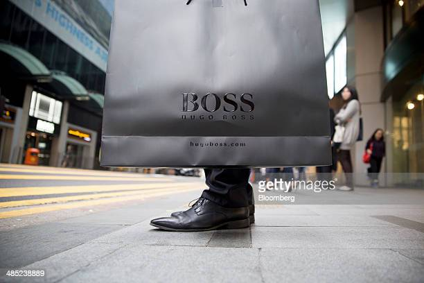 A man holds a Hugo Boss AG bag in the Central district of Hong Kong China on Wednesday April 16 2014 Socalled affordable luxury brands such as Coach...