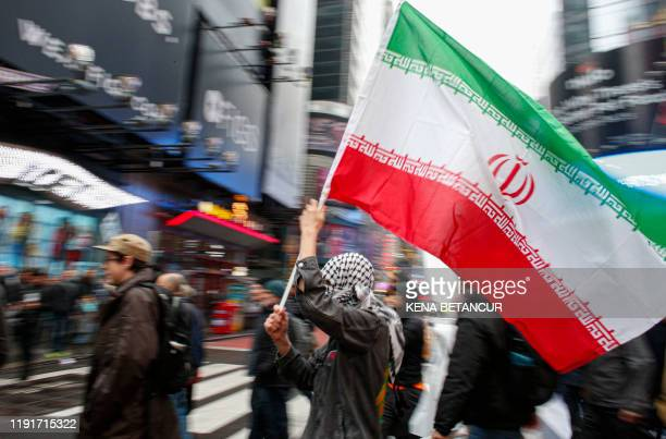 A man holds a Iranian flag during an antiwar protest at Times Square in New York on January 4 2020 Demonstrators are protesting the US drone attack...