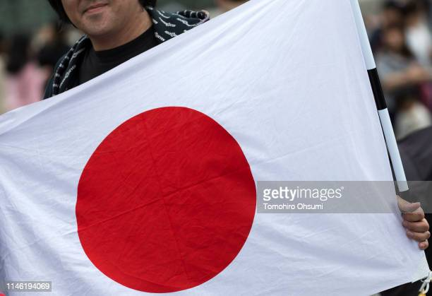 A man holds a Japanese national flag in front of the Imperial Palace on May 1 2019 in Tokyo Japan Emperor Naruhito formally took up the Chrysanthemum...