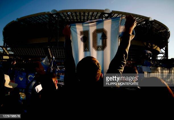 Man holds a jersey of Argentina's national football team with Diego Maradona's number 10 as people gather outside the San Paolo stadium in Naples on...