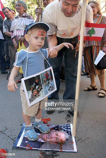 A man holds a kid as he dirties a picture of US President George W Bush during a protest rally against the Israeli offensive in Lebanon near the US...