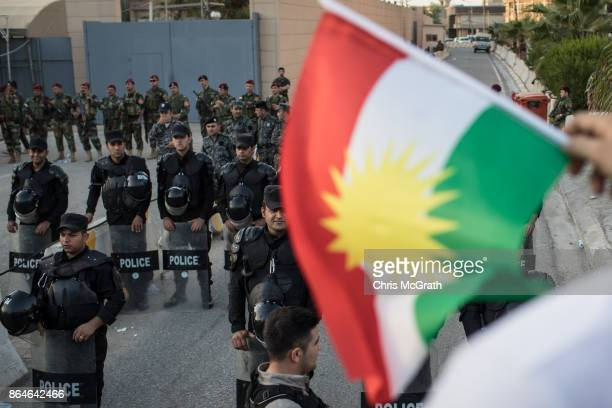 Man holds a Kurdish flag in front of police and security forces during a protest outside the US Consulate on October 21, 2017 in Erbil, Iraq. The...