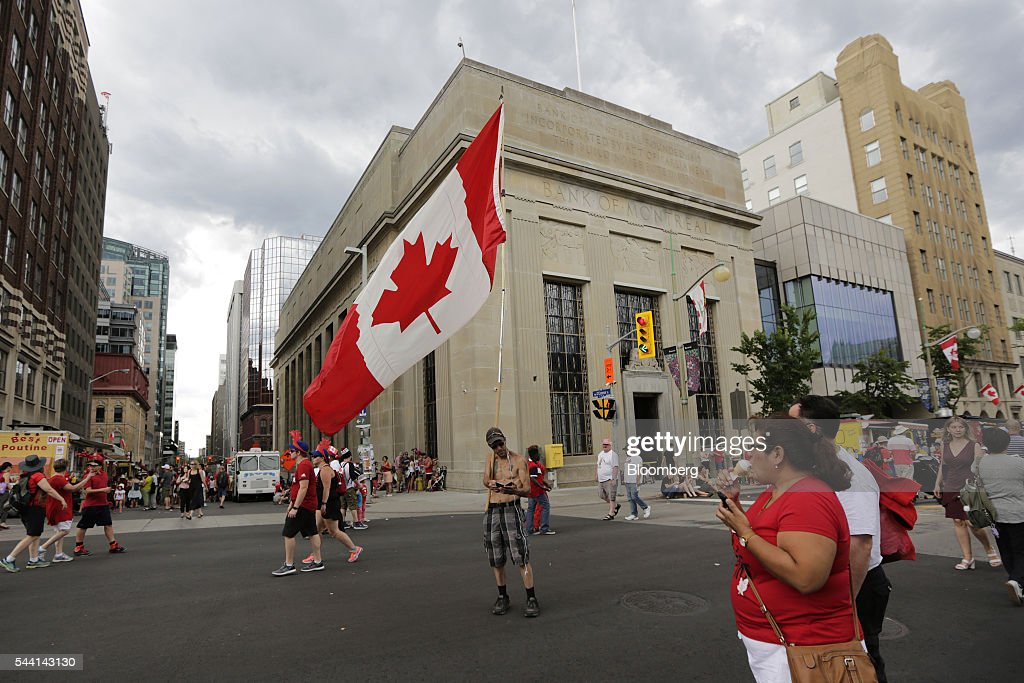A man holds a large Canadian flag while standing on Wellington Street on Canada Day in Ottawa, Ontario, Canada, on Friday, July 1, 2016. On July 1, thousands of locals and tourists gather in Ottawa's downtown area to celebrate. This year marks Canada's 149th birthday and Justin Trudeau's first Canada Day as Prime Minister. Photographer: David Kawai/Bloomberg via Getty Images