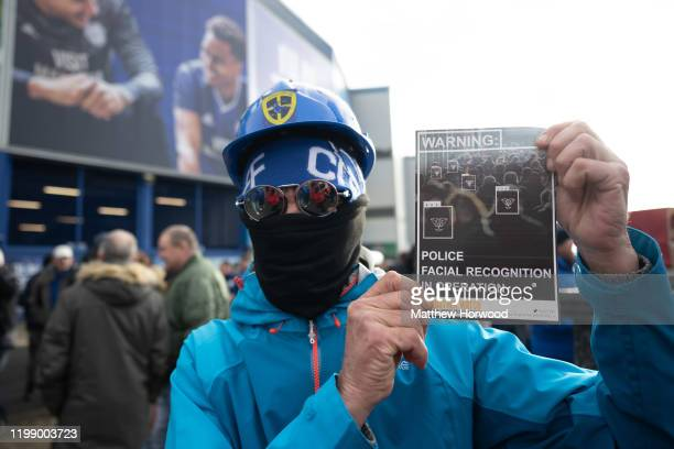 A man holds a leaflet during a protest against the use of police facial recognition cameras at the Cardiff City Stadium for the Cardiff City v...